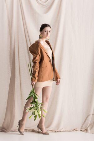 Belle femme avec des fleurs dans les mains debout sur fond de rideau Banque d'images
