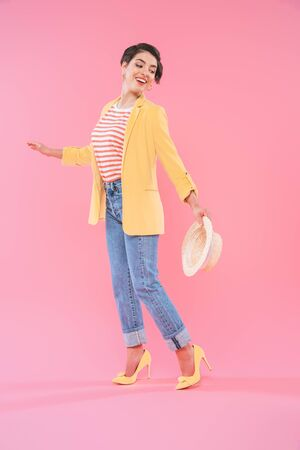 Attractive mixed race woman in bright clothing posing at camera on pink background Banco de Imagens