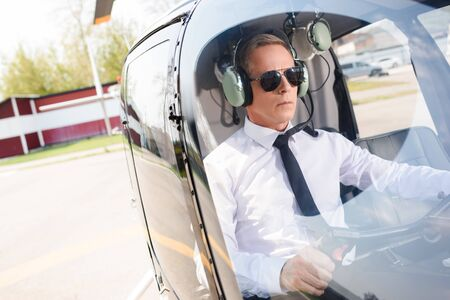 Mature Pilot in formal wear and headset sitting in helicopter cabin Stok Fotoğraf