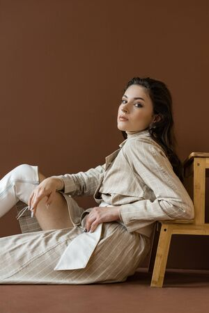 Stylish model in trendy trench coat sitting on floor with brown background, looking at camera