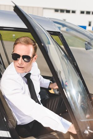 Handsome Pilot in sunglasses and formal wear sitting in helicopter cabin and opening door Stok Fotoğraf