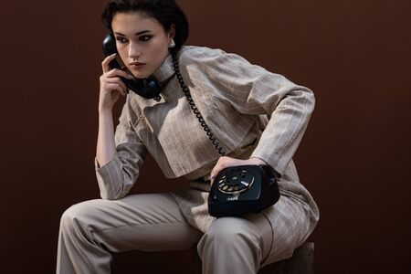 Trendy model with handset in hand sitting on brown background, looking away