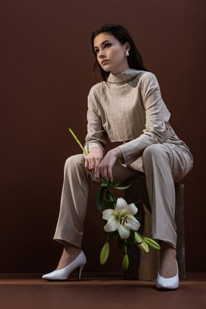 Low angle view of model with flower in hands sitting on box, looking away