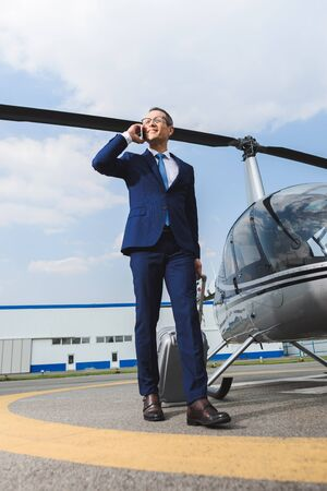 Businessman in formal wear with suitcase talking on smartphone near helicopter