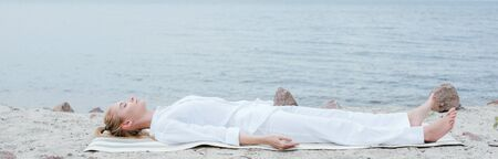 Panoramic shot of attractive blonde woman with closed eyes meditating while lying on yoga mat near sea