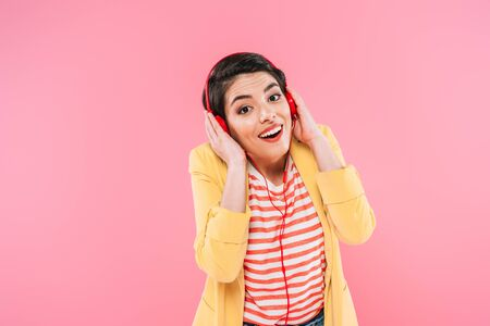 Excited mixed race woman listening music in headphones isolated on pink background Banco de Imagens