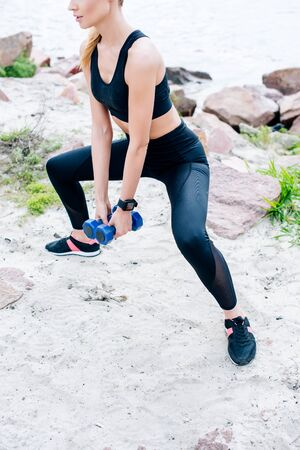 Cropped view of athletic young woman working out with dumbbells