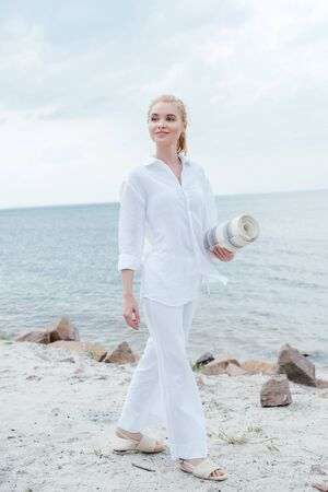 Happy blonde woman holding yoga mat and standing near sea Stock Photo