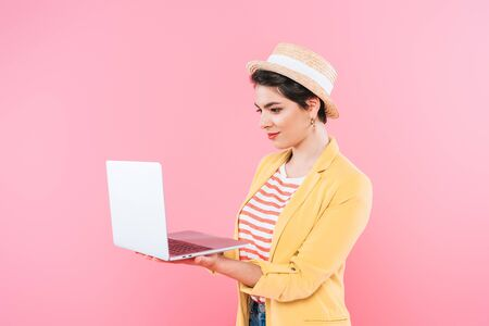 Attractive mixed race woman in straw hat using laptop isolated on pink background