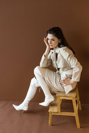 High angle view of trendy model in stylish trench coat looking away, sitting on stairs