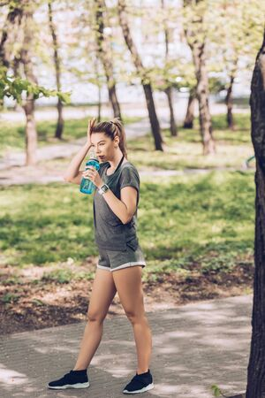 Attractive young woman in sportswear drinking from sport bottle in park