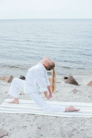 Attractive blonde  young woman doing yoga near sea