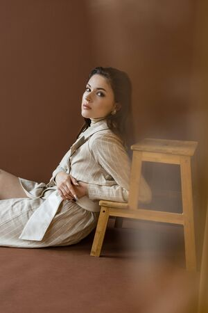 Side view of stylish woman in trendy trench coat looking at camera, sitting on floor near wooden stairs