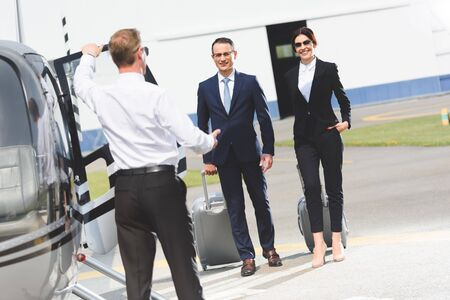 Business partners with luggage near pilot and helicopter