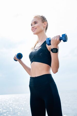 Low angle view of cheerful athletic girl working out with dumbbells near sea