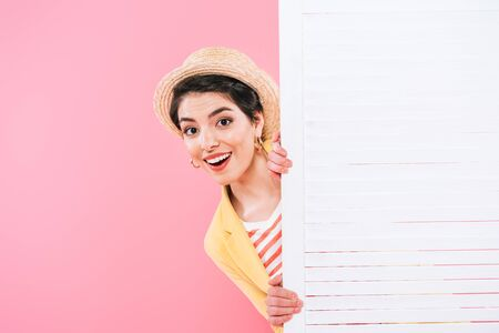 Cheerful mixed race woman looking out folding screen on pink background Banco de Imagens