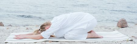 Panoramic shot of blonde young woman relaxing and practicing yoga on yoga mat near sea