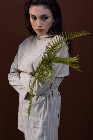 Model holding fern leaves in hands, looking away, standing on brown background
