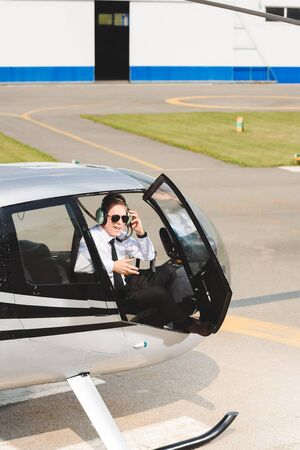 Mature Pilot in formal wear and sunglasses sitting in helicopter cabin with open door Stok Fotoğraf