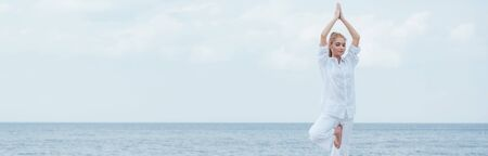 Panoramic shot of blonde woman with closed eyes practicing yoga