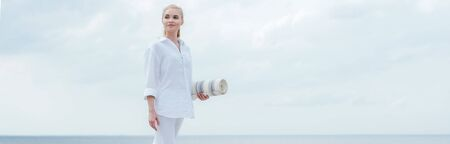Panoramic shot of happy young blonde woman standing near sea and holding yoga mat