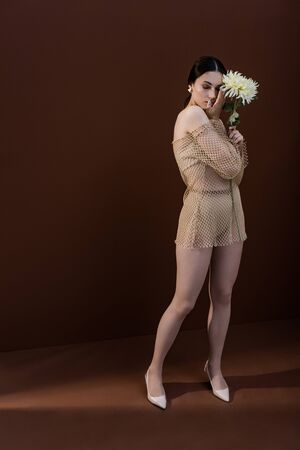Model with flower in hands closing eyes, standing on brown background Stok Fotoğraf