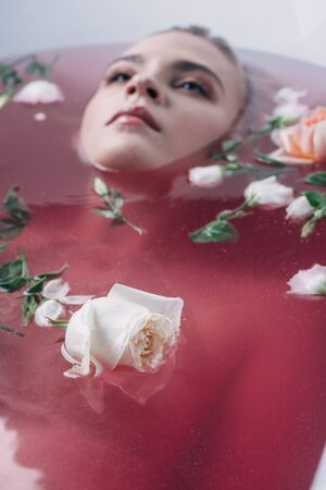 Selective focus of beautiful young woman lying in bathtub with colored pink water and roses