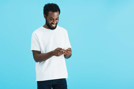Happy African American man using smartphone, isolated on blue background
