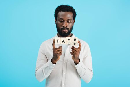 Young African American man holding alphabet cubes with fact word, isolated on blue background