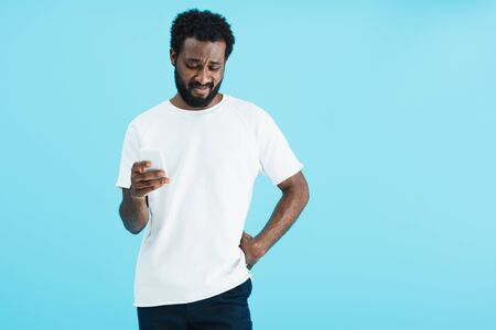 Confused African American man using smartphone, isolated on blue background