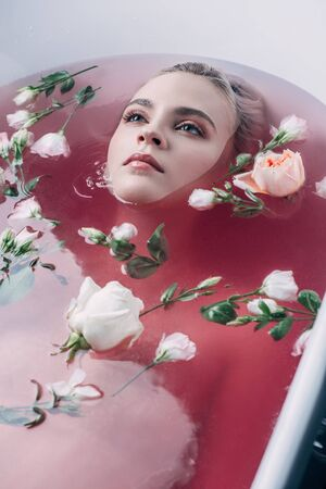 Beautiful young woman lying in bathtub with colored pink water and flowers and looking away