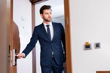 Opinión de ángulo baja, de, hombre guapo, entrar, habitación de hotel Foto de archivo