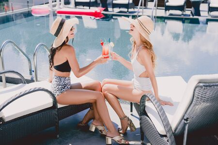 Blonde and brunette women in straw hats and swimsuits clinking with cocktails near swimming pool