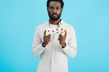 Serious African American man holding alphabet cubes with fact word, isolated on blue background