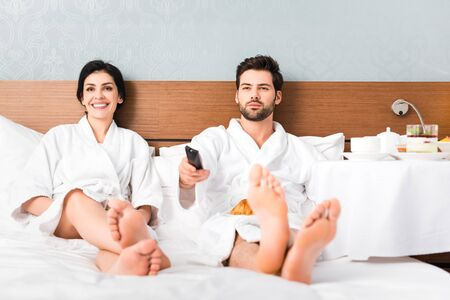 Selective focus of cheerful man holding remote controller near attractive woman in hotel room