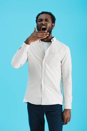 Tired African American man yawning isolated on blue background