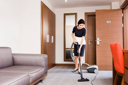 Attractive brunette housemaid cleaning carpet with vacuum cleaner in hotel room
