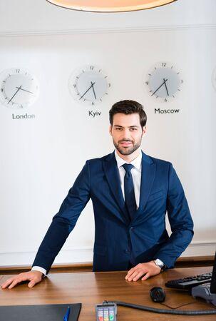 Cheerful bearded receptionist standing at reception desk in hotel Zdjęcie Seryjne