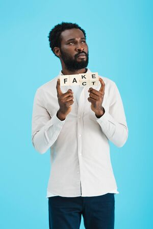 Thoughtful African American man holding alphabet cubes with fact word, isolated on blue background