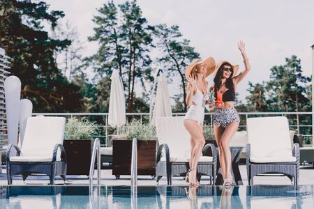 Two pretty girls waving hands and holding cocktails near swimming pool Stock Photo
