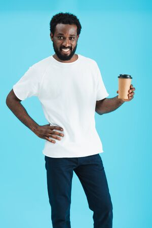 Happy African American man holding coffee to go, isolated on blue background