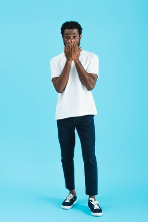 Worried African American man in white t-shirt closing face, isolated on blue background Stock Photo