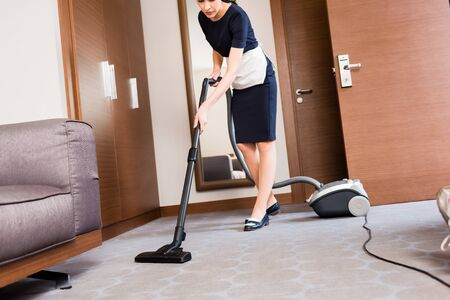Cropped view of housemaid cleaning carpet with vacuum cleaner in hotel room