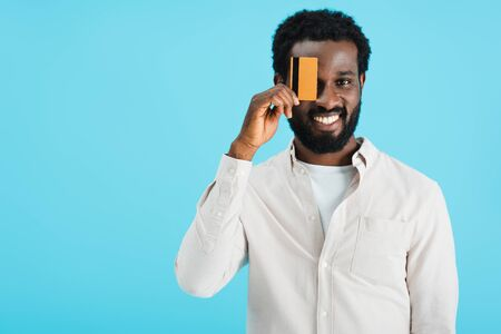 Happy African American man showing credit card isolated on blue background