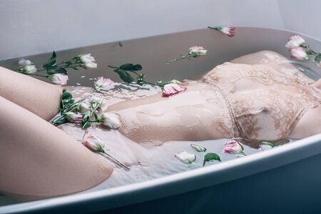 Cropped view of sexy woman in beige lace underwear lying in clear water with flowers in white bathtub