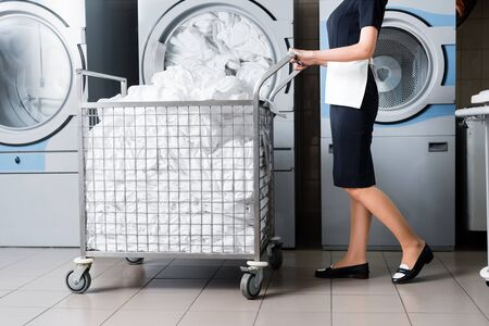 cropped view of housemaid standing near cart with bedding in laundry Banco de Imagens