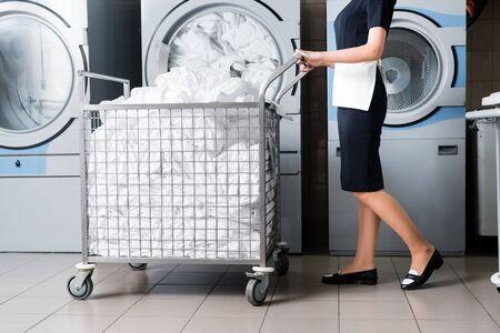 Vista recortada de la criada de pie cerca del carro con ropa de cama en la lavandería