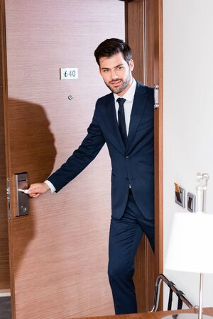 Cheerful and bearded businessman in suit entering hotel room