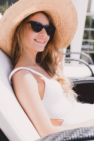 happy blonde woman in straw hat and sunglasses sunbathing on lounger