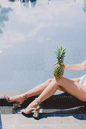 Partial view of sexy woman sitting near swimming pool in white swimsuit with pineapple